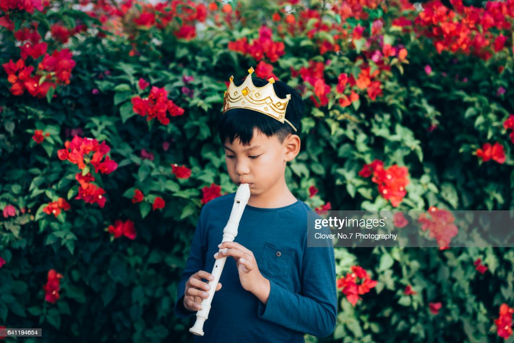 Asian boys play the flute, wearing a crown in the beautiful garden. : Stock Photo