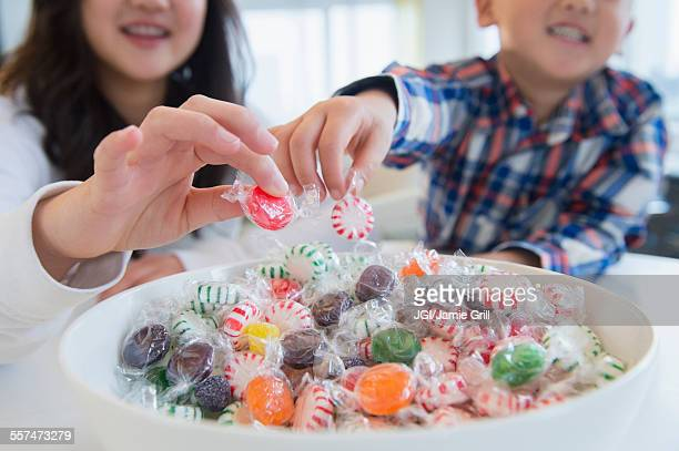 asian brother and sister picking candy from bowl - bowl of candy stock photos and pictures