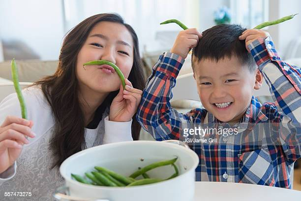 Asian brother and sister playing with vegetables