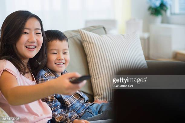 Asian brother and sister watching television on sofa
