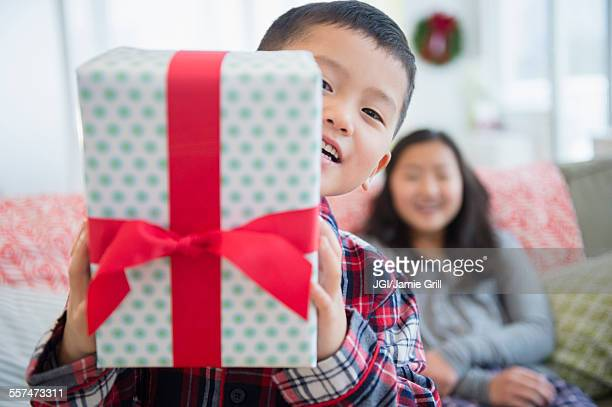 Asian brother with sister holding Christmas gift