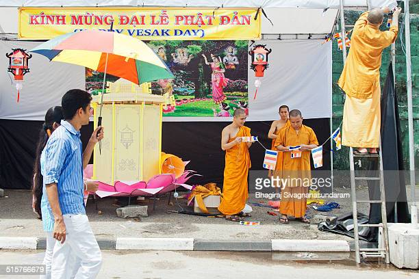 Asian Buddhist monks doing decorations with lanterns to celebrate upcoming vesak festival in Sri Lanka