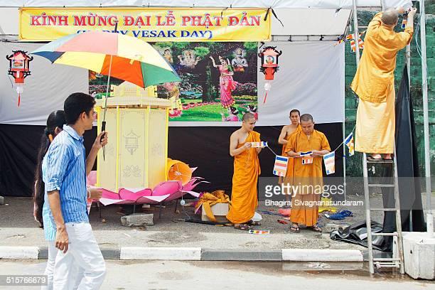 Asian Buddhist monks doing decorations with lanterns to celebrate upcoming vesak festival in Sri Lanka