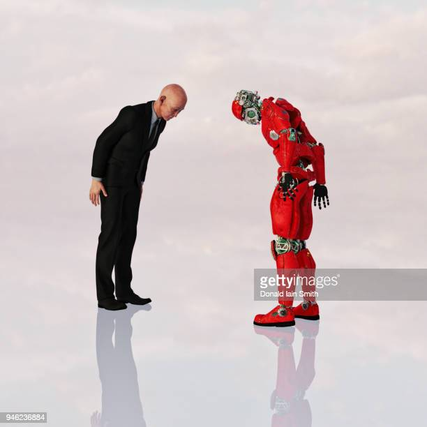Oriental business man and robot bow towards each other