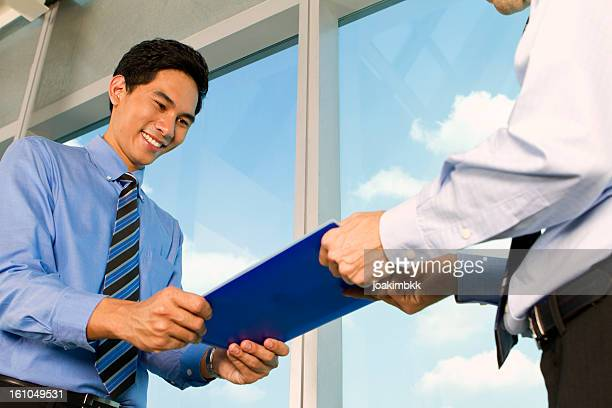 Asian business man handing over documents