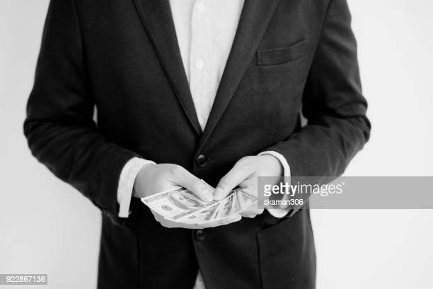 Asian Business man offer money us dollar and show thumb up
