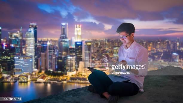 asien-geschäftsmann mit laptop und digital-tablette in singapur - marina bay singapur stock-fotos und bilder