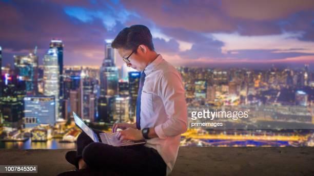 ラップトップ コンピューターおよびシンガポールでデジタル タブレットを使用してアジア ビジネス人 - シンガポール文化 ストックフォトと画像