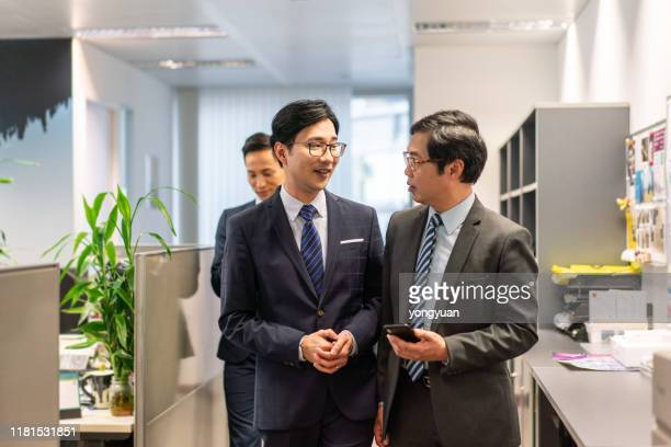 asian business people walking and talking in office - formal businesswear stock pictures, royalty-free photos & images