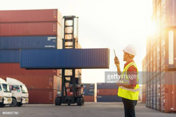 Asian business supervisor and secretary of Foreman control loading Containers from Cargo freight ship for import export in the transportaion industrial by truck and container ship. Industrial concept.