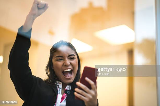 asian business woman celebrating with mobile phone - college application stock photos and pictures