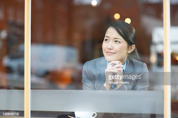 Asian business woman looking out of cafe window.