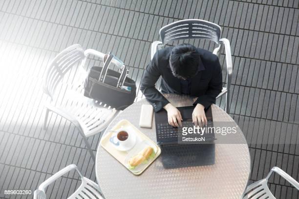 アジアのビジネスの女性は、オーバーヘッドのビューのカフェでランチ時間