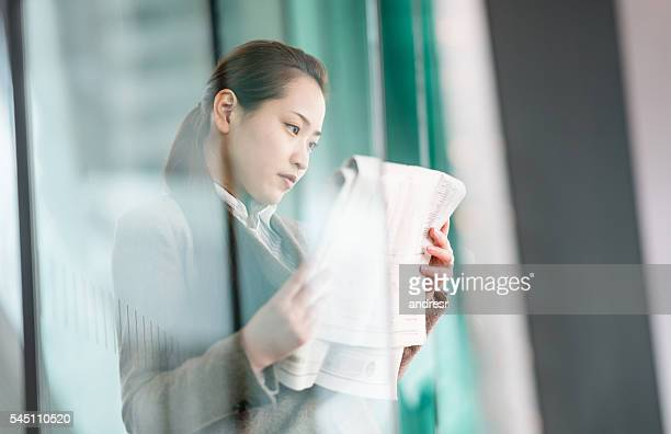 Asian business woman reading the news