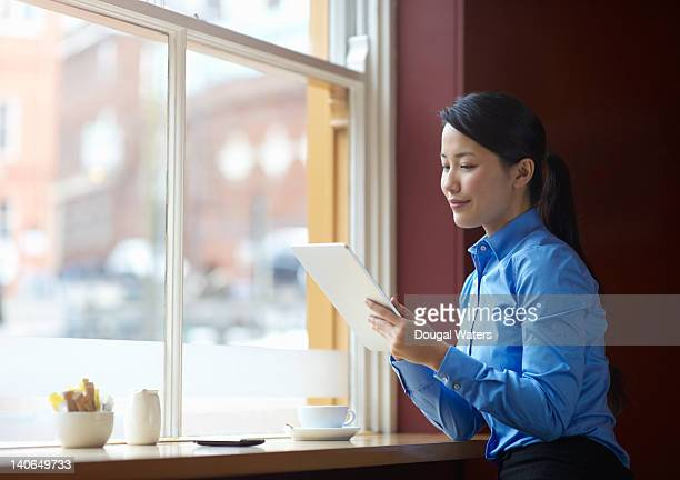 Asian business woman using digital tablet in cafe.