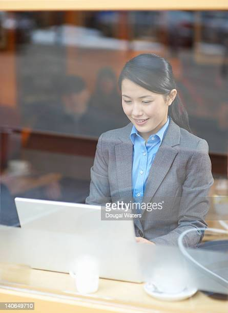 Asian business woman using laptop in cafe.