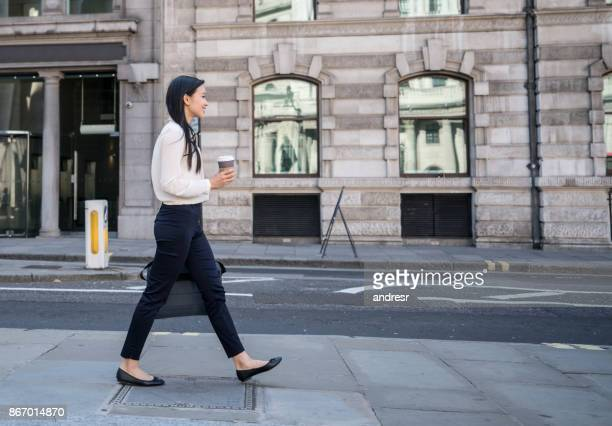 Asian business woman walking on the street drinking a cup of coffee