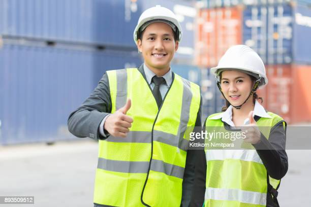 Asian businessman and Asian secretary  working  inspecting on-line device in yard in container Cargo freight ship in shipyard for Logistic Import Export background