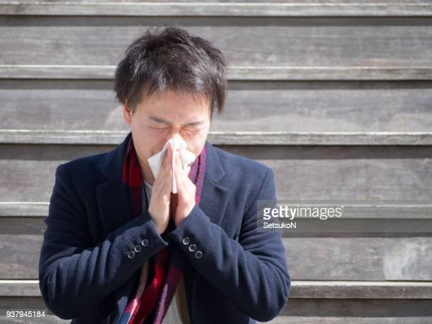 アジア系のビジネスマンが彼の鼻を吹く屋外 - くしゃみ ストックフォトと画像