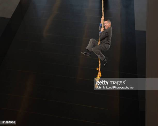 Asian businessman dangling from end of rope