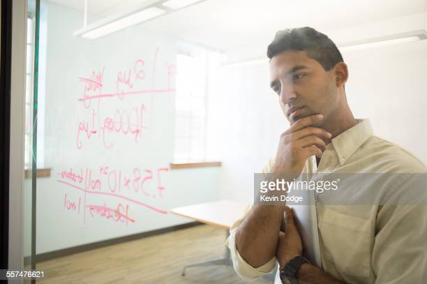 Asian businessman examining writing on glass window in office