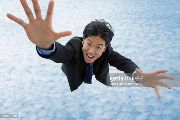 asian businessman falling in sky - 手を伸ばす 男性 ストックフォトと画像