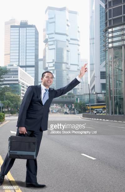Asian businessman hailing taxi