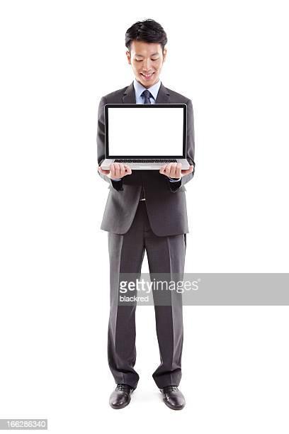 アジアの実業家保有ラップトップコンピュータ