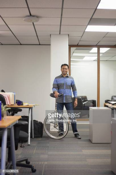 Asian businessman holding unicycle in office