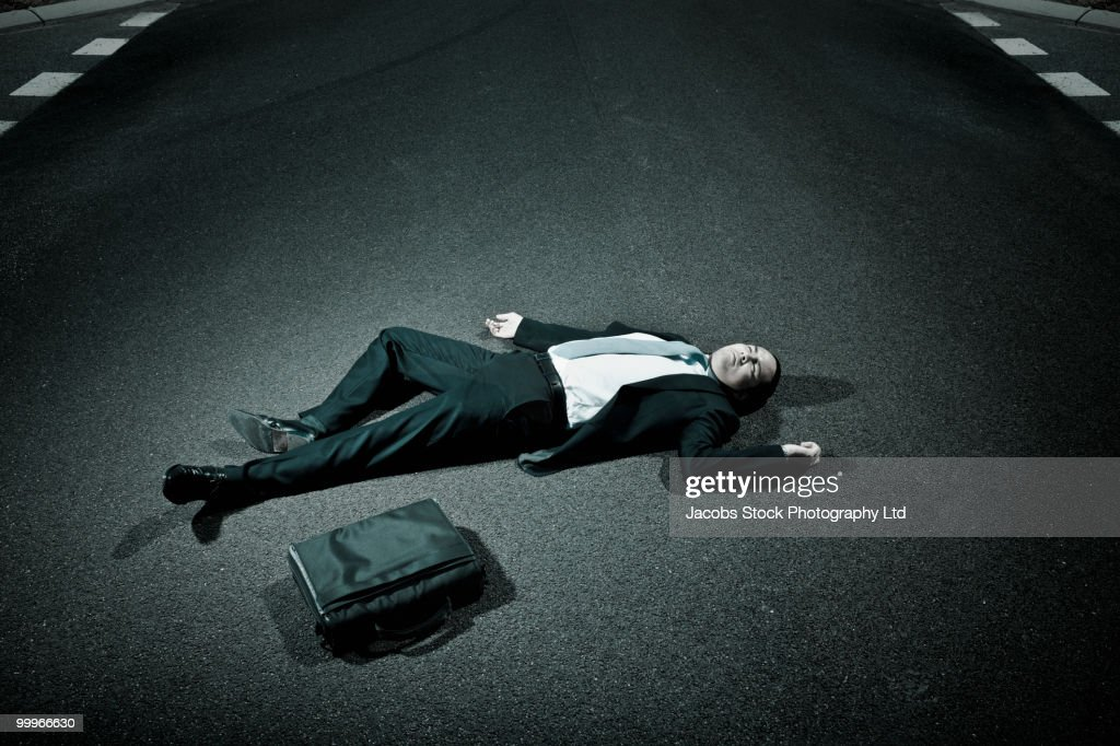 Asian businessman laying on asphalt roadway : Stock Photo