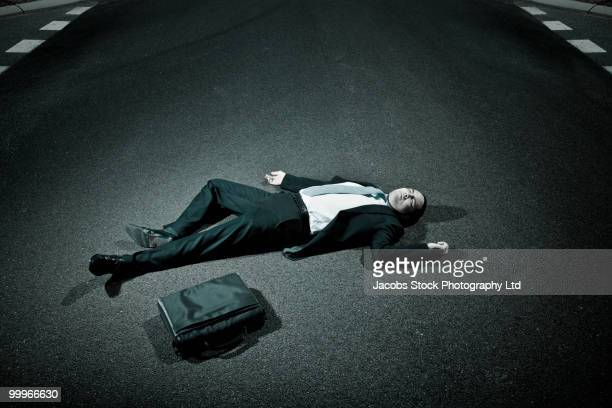 asian businessman laying on asphalt roadway - collapsing stock pictures, royalty-free photos & images