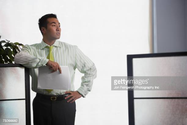 Asian businessman leaning on cubicle wall
