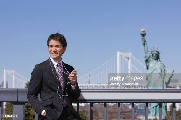 Asian businessman listening to mp3 player