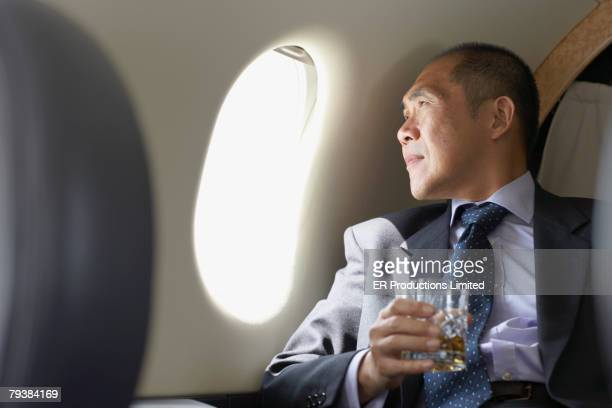 Asian businessman looking out airplane window
