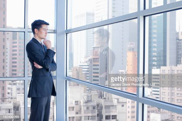 Asian businessman looking out office window