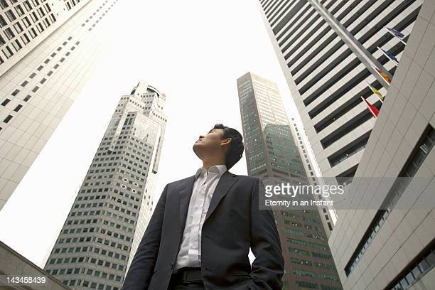 Asian Businessman looking up at  buildings in city
