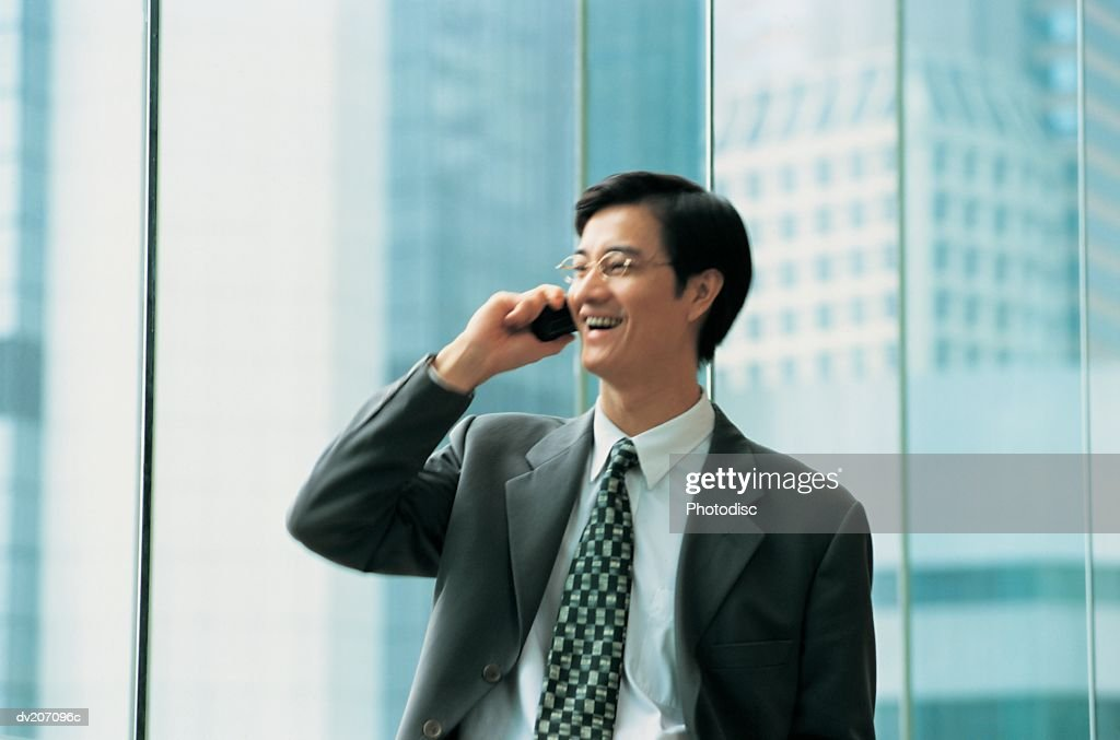 Asian businessman on cell phone : Stock Photo