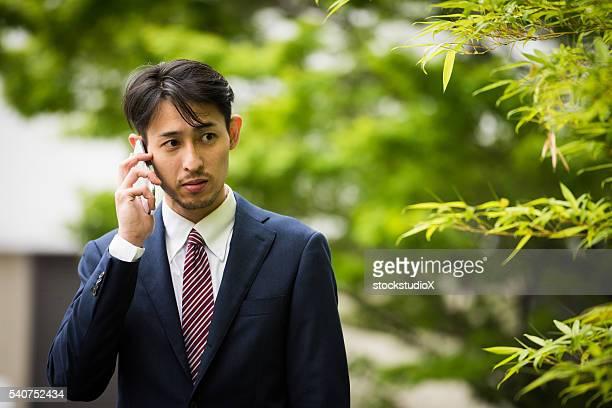 アジアのビジネスマンの電話
