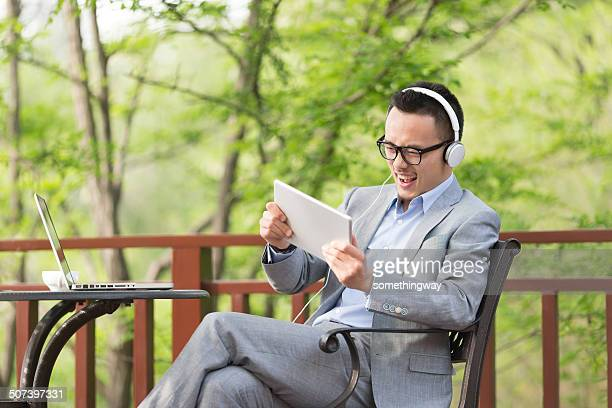 asian businessman play video games  in the outdoor coffee hall - handheld video game stock pictures, royalty-free photos & images
