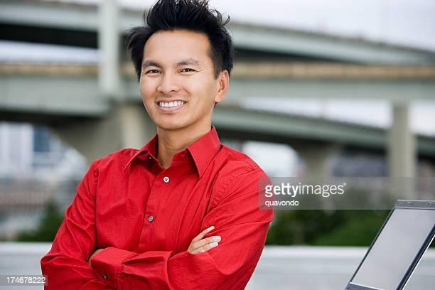 Portrait en plein air Homme d'affaires asiatique de traverser les bras, à l'aide d'un ordinateur portable