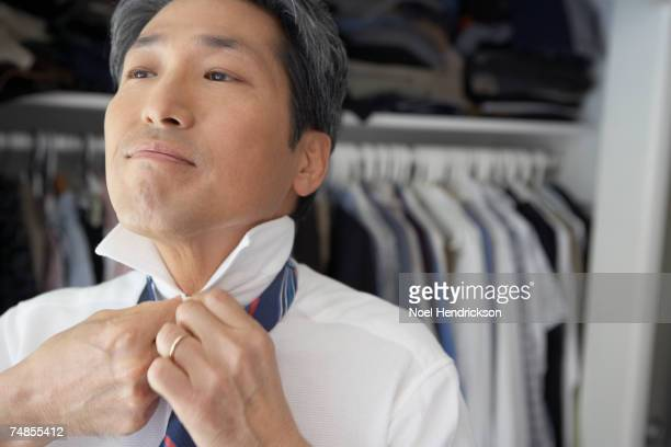 Asian businessman putting on tie