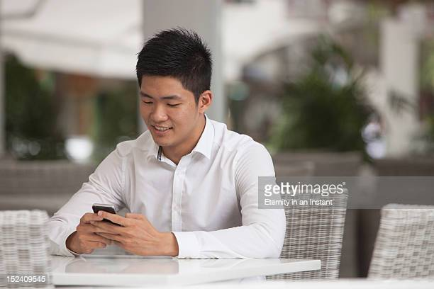 asian businessman sitting at cafe with smartphone - newtechnology stock pictures, royalty-free photos & images