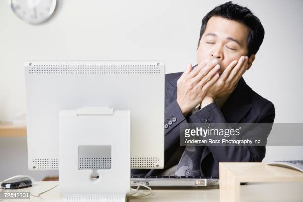 asian businessman sitting at computer yawning - mid adult men stock pictures, royalty-free photos & images