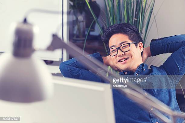 Asian businessman sitting at his desk relaxing