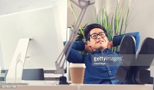 Asiatique Homme d'affaires, assis à son bureau, détente