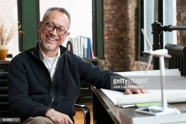 Asian businessman smiling with blueprints in office