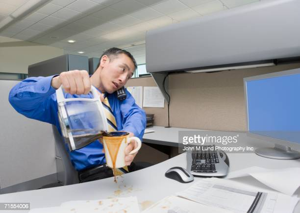 asian businessman spilling coffee on desk - spilling stock pictures, royalty-free photos & images
