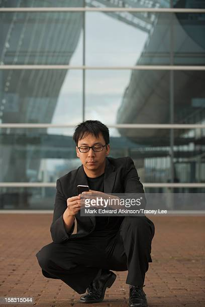 Asian businessman squatting and text messaging on cell phone