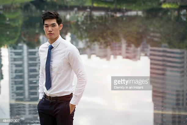 Asian businessman standing in front of a lake