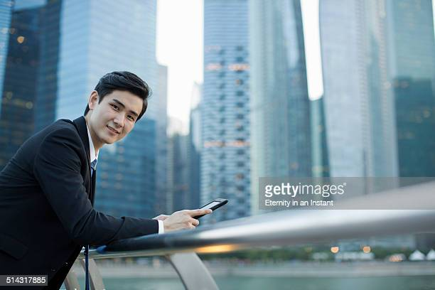 Asian businessman standing in front of buildings.